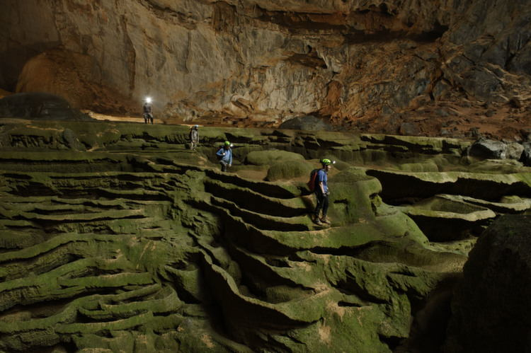 Hang Son Doong explorers navigate an algae-covered cavescape.